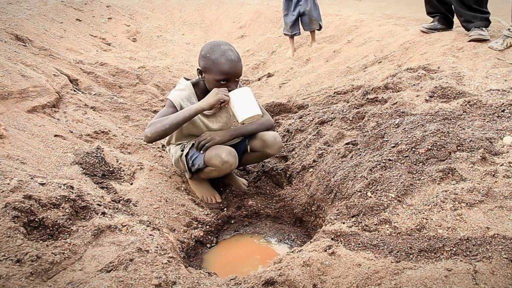 Ребенок в Кении пьет воду из лужи
